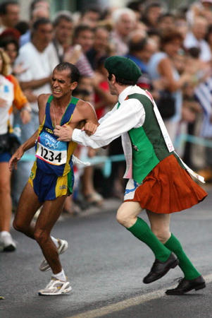 Vanderlei Lima of Brazil is attacked by a spectator in the latter stages of the marathon, the final event of the Olympic Games in Athens, 29 August 2004.The Brazilian, who was expected to win the gold, finished in third place winning the bronze. AFP PHOTO / JIRO MOCHIZUKI